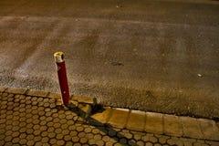 Ein roter Straßenpfosten und Autolichter, welche die Straße fegen Stockfoto