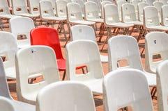 Ein roter Stuhl umgeben mit weißen Stühlen Lizenzfreie Stockfotos