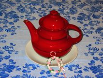Ein roter Teetopf der Schönheit auf einem blauen geblühten Segeltuch lizenzfreie stockbilder