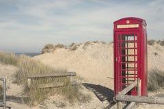 Ein roter Telefon-Kasten auf Sanddünen in Dorset lizenzfreie stockfotos