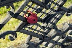 Ein roter Verschluss in Form eines Herzens befestigt zu einem Zaun Das symbo Lizenzfreie Stockbilder