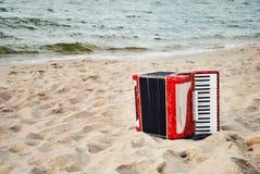 Ein rotes Akkordeon auf einem Strand lizenzfreies stockfoto