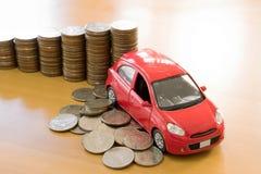 Ein rotes Auto über vielen Staplungsmünzen Lizenzfreies Stockfoto