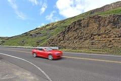 Ein rotes Auto auf einer der hawaiischen Landstraßen Lizenzfreies Stockfoto