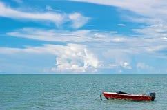 Ein rotes Boot im Ozean mit blauem Himmel stockfoto