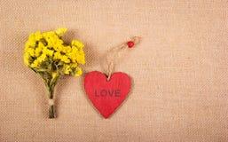 Ein rotes hölzernes Herz und ein Blumenstrauß des Gelbs auf einem natürlichen Leinenhintergrund Romantisches Konzept Hintergründe Lizenzfreies Stockfoto