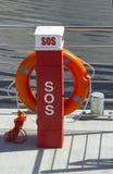 Ein rotes Leben, das Schwimmweste auf einem sich hin- und herbewegenden Ponton konserviert Lizenzfreie Stockbilder