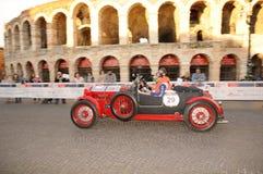 Ein rotes und schwarzes Lancia-Lambda VII fährt vor den Arenadi Verona Stockbild