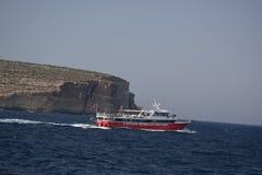 Ein rotes und weißes Boot auf dem Ozean mit einem großen Seefelsen im Hintergrund lizenzfreie stockfotografie
