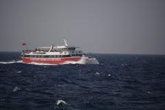 Ein rotes und weißes Boot auf dem Ozean mit einem Hintergrund des blauen Himmels stockfoto