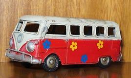 Ein rotes Zinnspielzeug Van oder Bus gemalt mit Blumen stockfotos