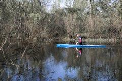 Ein Rudersport des jungen Mannes auf einem blauen Kanu auf einem ruhigen Fluss entlang dem Verbot Lizenzfreie Stockfotografie