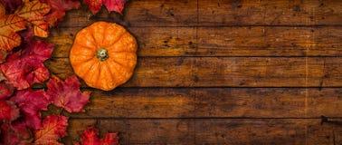 Ein rustikaler hölzerner Hintergrund mit Herbstlaub und einem Kürbis lizenzfreie stockfotos