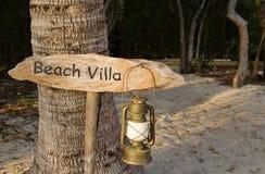 Ein rustikales Strandlandhauszeichen mit Öllampe Stockbild