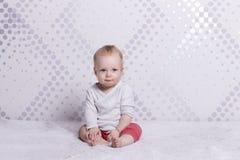 Ein Säuglingsjunge, der Kamera sitzt und betrachtet entziehen Sie Hintergrund Lizenzfreies Stockfoto