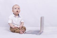 Ein Säuglingsjunge in einem Hemd mit Laptop Kind, das oben looiking ist Stockfotos