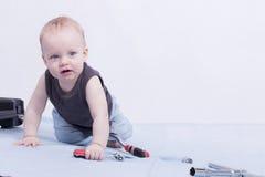 Ein Säuglingsjunge mit Satz Instrumenten, die auf dem blauen Teppich sitzen Lizenzfreie Stockbilder
