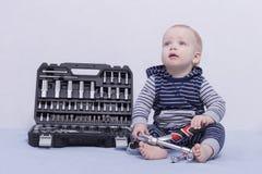 Ein Säuglingsjunge mit Werkzeugkasten und justierbarem Schlüssel in seinen Händen Horizontale Atelieraufnahme Konzept für Bauwese Lizenzfreies Stockbild