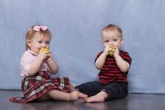 Ein Säuglingsjunge und ein entzückendes kleines Mädchen, die auf dem Boden mit Äpfeln sitzen Stockbild