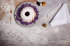 Ein süßer Kuchen mit Blumen auf einer Platte Eine Zusammensetzung des neuen Jahres auf einem grauen Hintergrund Die Aufschrift 20 Stockbilder