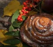 Ein süßes Brötchen mit Rosinen, Aschbeeren, Äpfeln und buntem Herbstlaub auf einer Steinoberfläche Stockfotografie