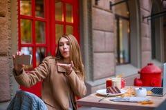 Ein süßes junges Mädchen, sitzend in einem Café, machen selfie an einem Handy und senden einen Luftkuß lizenzfreies stockfoto