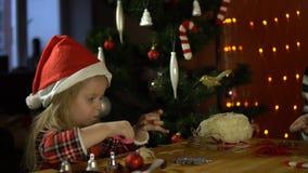 Ein süßes kleines Mädchen in einem Sankt-` s roten Hut macht Schmuck für den Weihnachtsbaum stock video