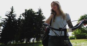 Ein süßes Mädchen beantwortet einen Telefonanruf im Park stock video