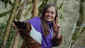 Ein süßes Mädchen macht einen Frieden-selfie auf dem Hintergrund der moosbedeckten Bäume in einem nebeligen Buchsbaumwald stock video