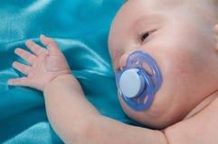 Ein süßes Schätzchen, das auf einem blauen Blatt schläft lizenzfreies stockfoto
