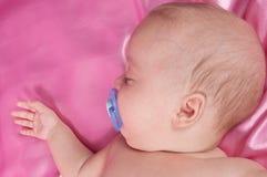 Ein süßes Schätzchen, das auf einem rosafarbenen Blatt schläft Stockbild
