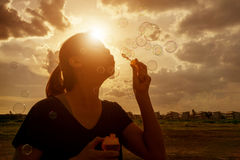 Ein südostasiatisches Mädchen brennt Blasen in die Luft am sunse durch Stockfoto