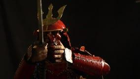 Ein Samurai in der roten Rüstung, in einem Sturzhelm und in einer defensiven Maske in Form eines Dämons fängt die Palme des katan