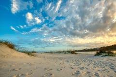 Ein sandiger Strand mit einem bewölkten Himmel lizenzfreies stockbild
