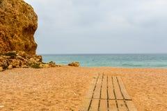 Ein sandiger Strand mit hölzernem Promenadenende in Meer Stockbilder