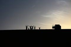 Ein Satz Abenteurer begrüßen von der Spitze einer großartigen Sanddüne beim Genießen eines schönen Sommersonnenuntergangs in Dakh Stockbild