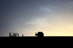 Ein Satz Abenteurer begrüßen von der Spitze einer großartigen Sanddüne beim Genießen eines schönen Sommersonnenuntergangs in Dakh Lizenzfreie Stockfotografie