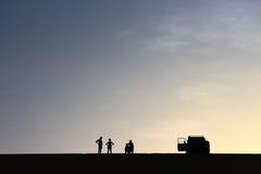 Ein Satz Abenteurer begrüßen von der Spitze einer großartigen Sanddüne beim Genießen eines schönen Sommersonnenuntergangs in Dakh Lizenzfreies Stockfoto
