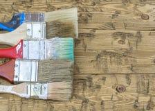 Ein Satz alte mehrfarbige Bürsten auf einem Holztisch Lizenzfreies Stockbild