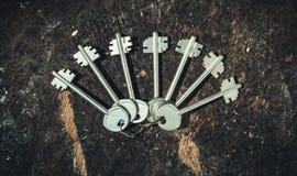 Ein Satz altmodische Schlüssel auf einem Hintergrund eines alten hölzernen Stumpfs Der Dekor in der rustikalen Art Stockbild