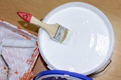 Ein Satz Ausrüstungen für Wohnungsreparatur, -malerei und -Design Bürste, Rolle, Behälter und Farbe können auf dem Boden lizenzfreies stockbild