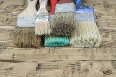 Ein Satz benutzte mehrfarbige Bürsten auf einem Holztisch Lizenzfreie Stockbilder