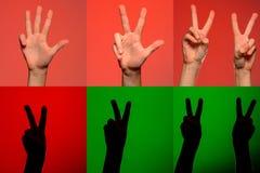 Ein Satz Charaktere auf den Fingern von menschlichen Händen, die durch Schattenbilder auf einem lokalisierten grünen Hintergrun stockfotos