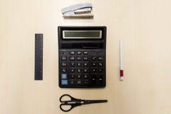Ein Satz des Büros bearbeitet das Bestehen aus einem Taschenrechner, Stift, Hefter, stockfoto
