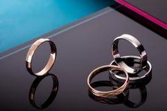 Ein Satz Eheringe mit Edelsteinen Auf modernem schwarzem glattem Hintergrund mit Reflexion Stockbild