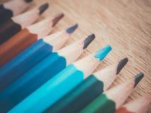 Ein Satz einiger farbiger Bleistifte Bleistifte in Folge auf einer Holzoberfläche Stockfotografie