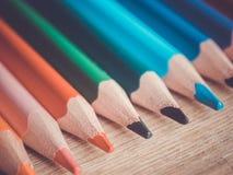 Ein Satz einiger farbiger Bleistifte Bleistifte in Folge auf einer Holzoberfläche Lizenzfreie Stockfotografie