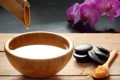 Ein Satz für Badekurortverfahren, heiße Massagesteine, Badesalz und gewürztes Wasser sammelte von einem Bambusstamm in eine Schüs lizenzfreies stockfoto