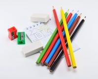 Ein Satz farbige Bleistifte mit Radiergummis, ein Bleistiftspitzer auf einem weißen Hintergrund Stockfotos