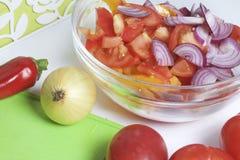 Ein Satz Gemüse für Salat liegt nahe dem Schneidebrett Messer für den Schnitt und ein Behälter für Salat Stockfotografie